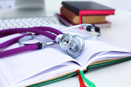 scientific literature: Stethoscope lying on a table on an open book.