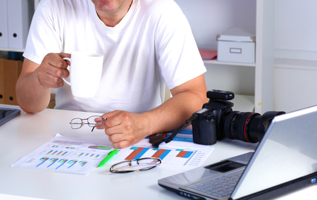 behind: a businessman behind a table with graphics. Stock Photo