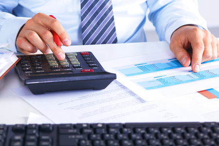 calculations: Big boss checks calculations on a calculator. Stock Photo