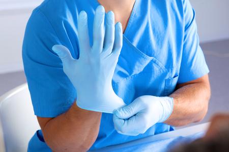 enfermera con cofia: Cirujano de ponerse los guantes antes de una operación de primer plano. Foto de archivo