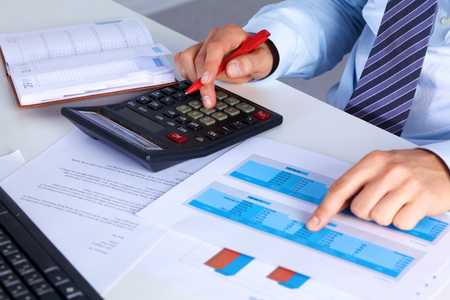 Big boss checks calculations on a calculator. Stock Photo