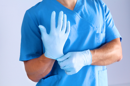 scrub cap: The surgeon wears gloves before surgery. Close-up. Stock Photo