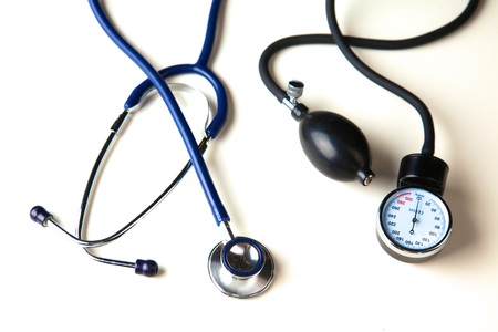 cuff: Medical stethoscope and blood pressure cuff on the table. Stock Photo