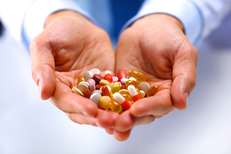 outstretched hand: young doctor holding pills in his outstretched hand packaging. Stock Photo