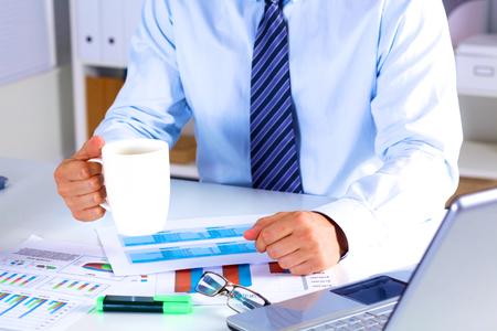 recursos financieros: businessman drinking tea at a table in the office.