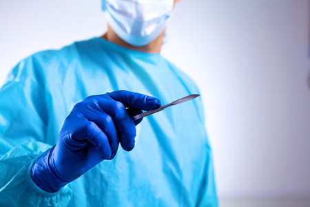 Young surgeon holding a scalpel. Ready for operation.