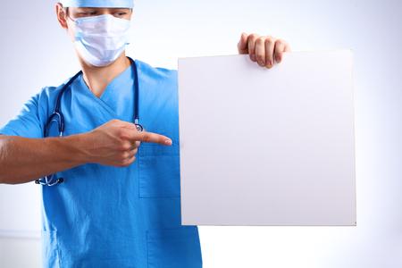 chirurg v masce drží transparent.