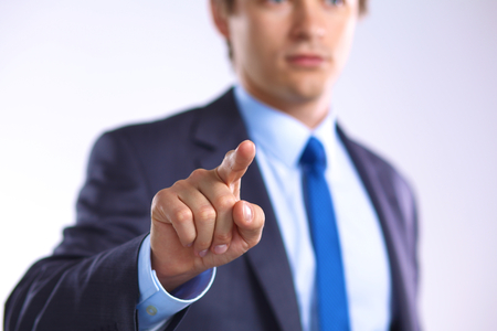 Young businessman points his finger at an object.