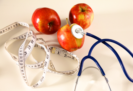 Stethoscope with red apples on a white background. Stock Photo