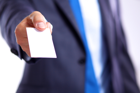 young businessman holds out his hand with a business card. Stock Photo