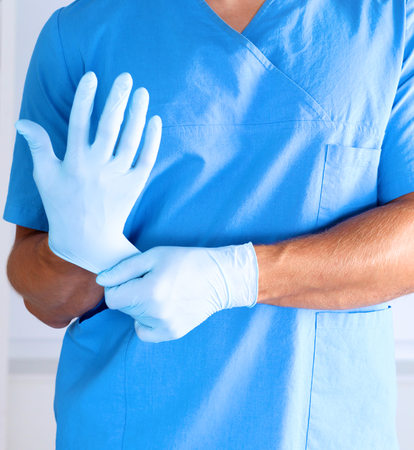 registered nurse: Surgeon putting on gloves before a close-up operation. Stock Photo