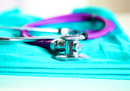 A stethoscope shaping a heart and a clipboard on a medical uniform, closeup. Stock Photo