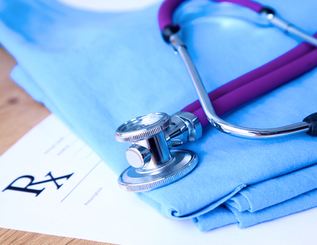 shaping: A stethoscope shaping a heart and a clipboard on a medical uniform, closeup. Stock Photo