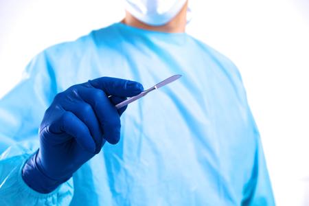 cirujano joven que sostiene un bisturí. Listo para el funcionamiento. Foto de archivo