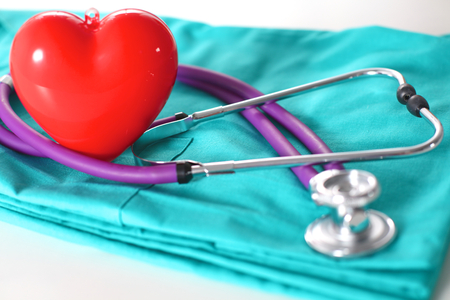 nurse hat: A stethoscope shaping a heart and a clipboard on a medical uniform, closeup. Stock Photo