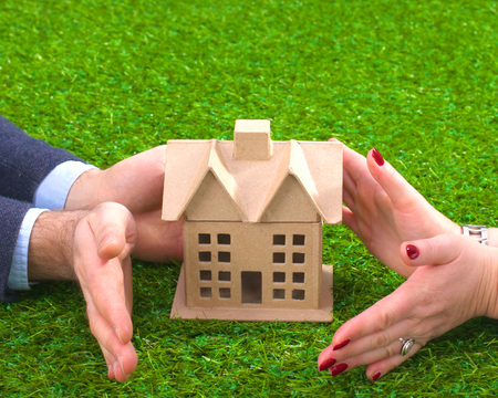 small roof: Female hands saving small house with a roof.