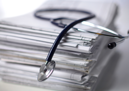 stack of papers: books folder file and stethoscope isolated on white background.