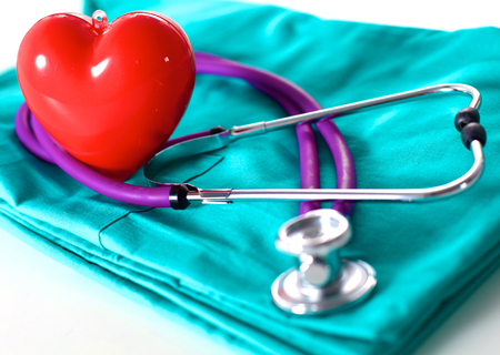 A stethoscope shaping a heart and a clipboard on a medical uniform, closeup. Foto de archivo