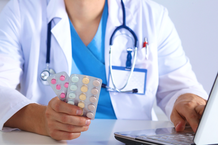 pharmacologist: Male medicine doctor hands hold jar of pills and type something on laptop computer keyboard. Panacea and life save, prescribing treatment, legal drug store, take stock, consumption statistics concept.