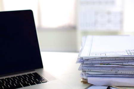 data archiving: Laptop with stack of folders on table on white background.