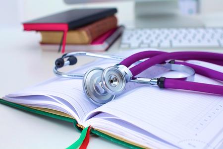 Stethoscoop die op een lijst een open boek ligt