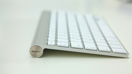 stylish aluminum keyboard lies on a white table