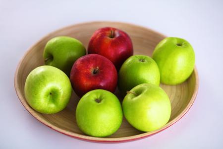 Still life arrangement of apples on a wooden platter
