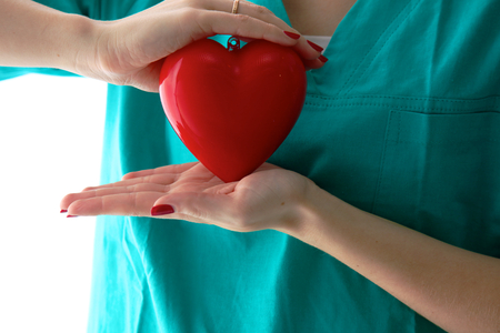 Dr. gently holding a heart on white background Stock Photo