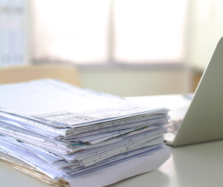 A stack of documentation is on the desktop in the office