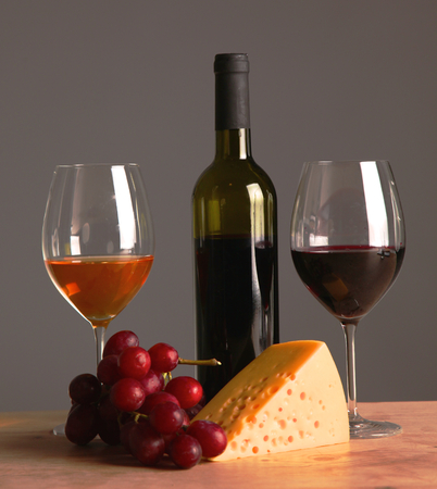 A bottle and a glass of wine on a table with fruit