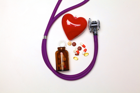 Close up of pills spread over the table with stethoscope and heart lying beside.