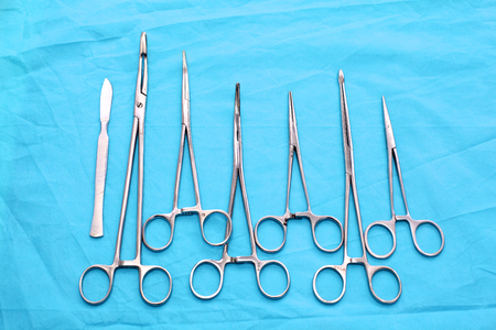 scalpels: surgical instruments and tools including scalpels, forceps and tweezers arranged on a table for a surgery.