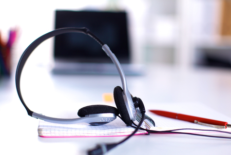 Call center service operator empty working place. Headset, glasses, keyboard and monitor at helpdesk employee workplace. Effective and efficient business information, help and support concept Stock Photo