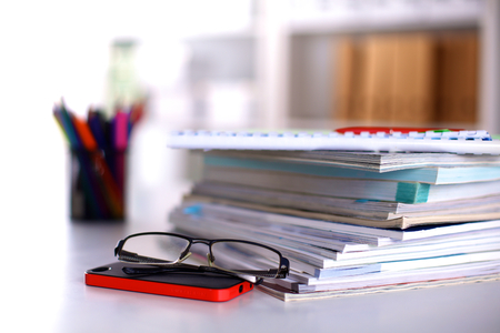 A stack of documentation is on the desktop in the office. Stock Photo