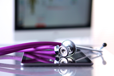 Tablet computer with a stethoscope lie on a table
