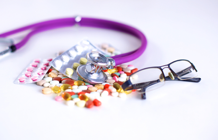 Close up of pills spread over the table with stethoscope and heart lying beside Stock Photo