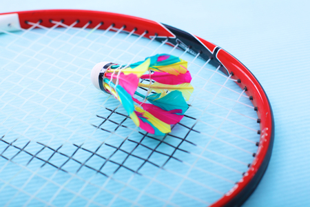 Close-up of badmington rackets with balls on a blue background