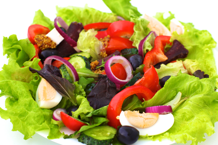 salad from fresh vegetables in a plate on a table, selective focus