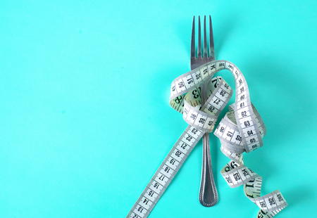 Fork with measuring tape. Dieting concept. On blue