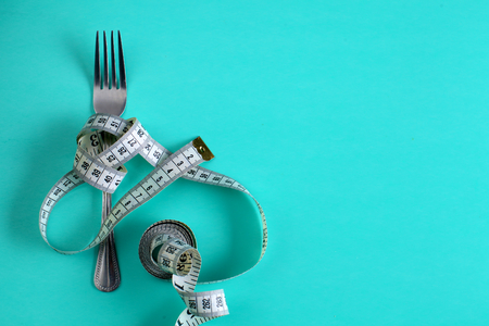 Fork with measuring tape. Dieting concept. On blue.