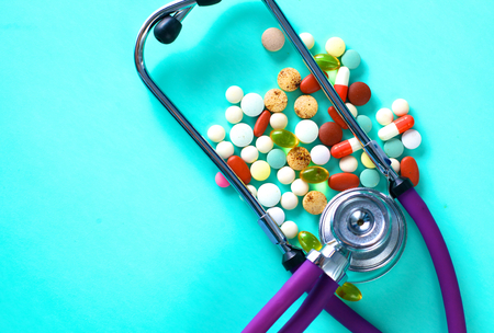 education: medical stethoscope with pills on a blue background