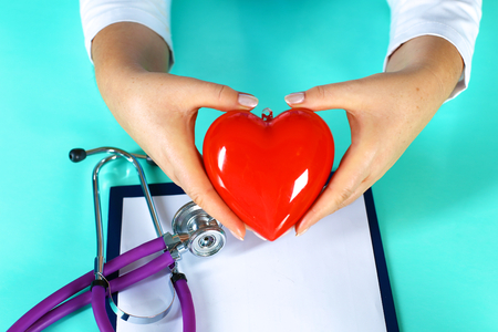 md: Female doctor with stethoscope holding heart. Doctor and patient sitting in the background
