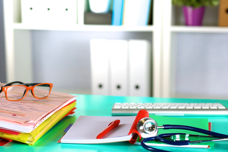 Doctors workspace working table with patients discharge blank paper form, medical prescription, stethoscope on desk