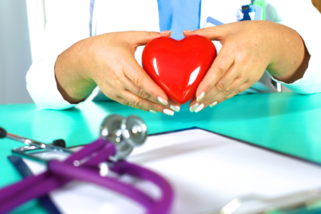 md: Woman doctor with a stethoscope holds a heart