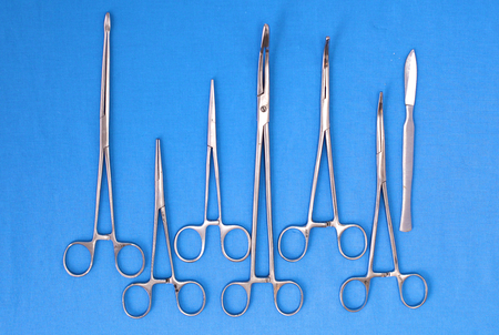 scalpels: surgical instruments and tools including scalpels, forceps and tweezers arranged on a table for a surgery