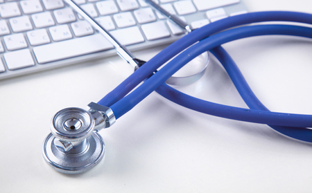 A medical stethoscope near a laptop on table, on white Stock Photo