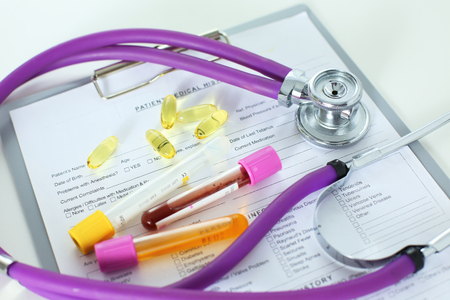 closeup of the desk of a doctors office with a stethoscope in the foreground and a bottle with pills in the background. Stock Photo