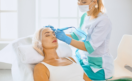 Permanent Makeup For Eyebrows. Beautiful Woman With Thick Brows In Beauty Salon. Beautician Doing Eyebrow Tattooing For Female Face. Beauty Procedure
