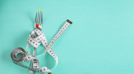 The fork is wrapped with a measuring tape on the table. Diet Reklamní fotografie