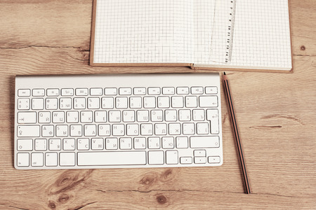 Modern aluminum keyboard on the wooden table in the office 스톡 콘텐츠